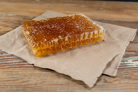 Angle View of Honey Comb on Brown Paper on wooden table