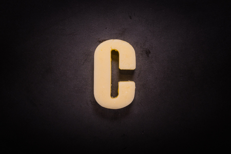 Butter Letter C on cast iron skillet background Stock Photo