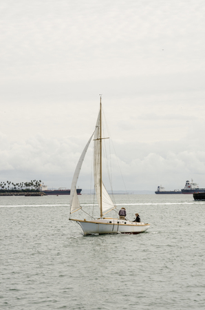 A sloop sail boat coasts along the calm waters of Long Beach harbor