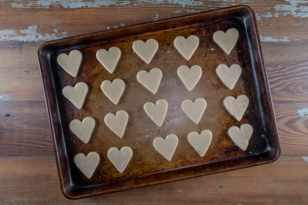 Raw Heart Cookies On Sheet Pan over wooden background