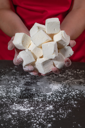 Large Group of Marshmallow Cubes in Hands of woman wearing red apron Stock Photo