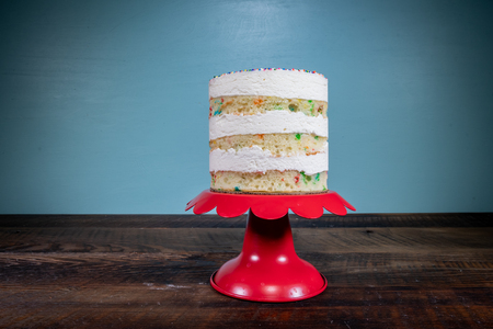 Three Tiered Naked Funfetti Cake On Red Cake Stand Centered