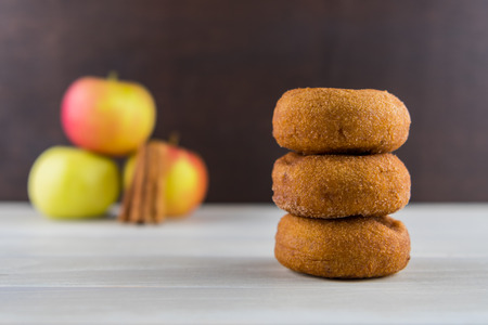 Stack of Three Apple Cider Donuts with Apples in Background