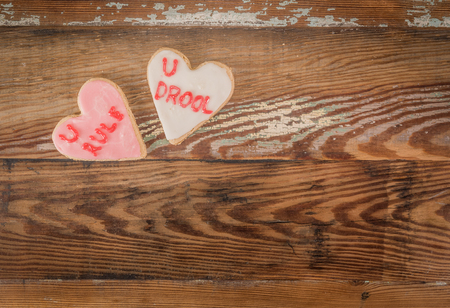 U Rule and U Drool Heart Cookie over wooden copy space Stock Photo