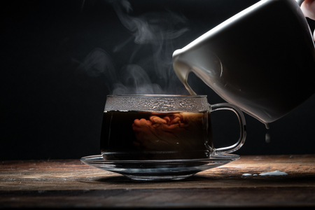 Pouring and Spilling Cream in Coffee in dark wooden table 免版税图像