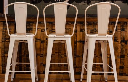 Three Tall Metal Stools at wooden bar Standard-Bild - 106377360