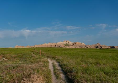 Trail Through Field Below Badlands Rock Formations