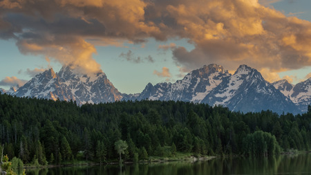 Clouds Hover over Tetons Range with Pine Trees in Foreground Stock Photo