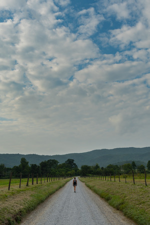 Land and Woman Walking Under Cloudy Sky in Late Summer Stock Photo