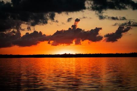 Orange Sky Glows Over Water as Sun Drops Behind the Horizon behind Rainy Lake