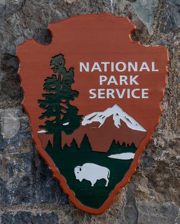Glacier National Park, United States: June 27, 2018: National Park Service Carved Sign on Stone Wall Editorial