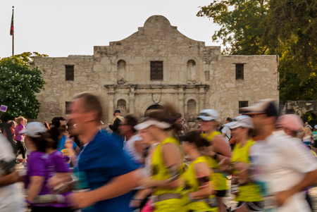 Blurs of marathon runners passing the Alamo during a race
