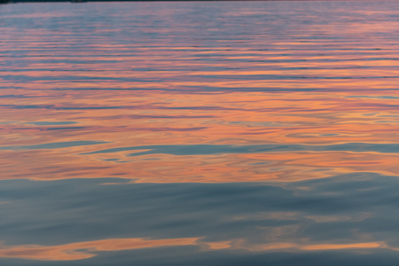 Pink Sunset Light Reflects on Ripples in Calm Water Stock Photo
