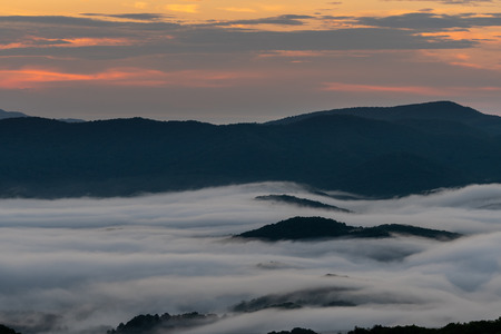 Pink Morning Light in Sky with Mountain Island Through Clouds in the Smokies Stock Photo
