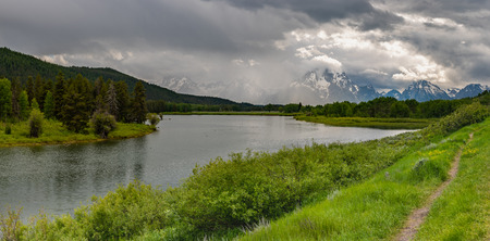 Thin Dirt Trail Along Heron Lake with Tetons in Distance Stockfoto
