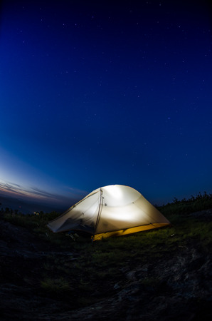 A lit tent against a navy blue sky with stars using a fisheye lens
