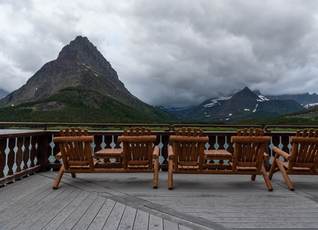Chairs On Many Glacier Hotel Deck with clouds behind Grinnell Point 版權商用圖片