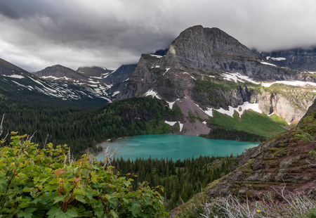 Foliage and Rock in Front of Grinnell Lake and Mountain Stock Photo
