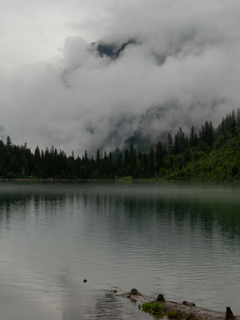 Fog Engulfs The Back Wall of Avalanche Lake in Montana wilderness