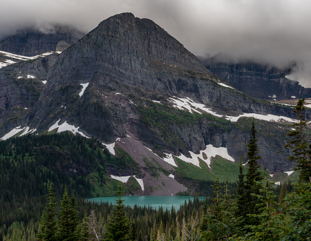 Grinnell Lake Peeks Through Forest on overcast day