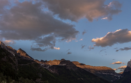 Pink Clouds Drift Above Logan Pass in late afternoon Stock Photo