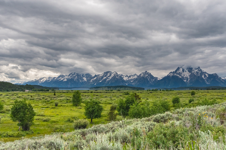 Tetons Wake in Summer with stormy clouds overhead 免版税图像