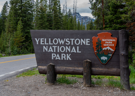 June 17, 2018: Yellowstone, United States: Yellowstone National Park Entrance Sign with Mountains in the Distance Editorial