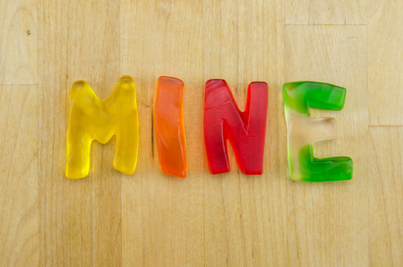 Multi colored gummy letters spell the word mine