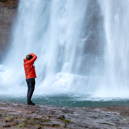 Man Standing Below Virgina Falls Taking Photos