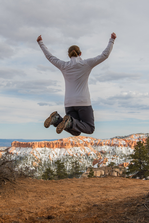 Woman Leaps for Joy at Edge of Bryce Canyon in Winter