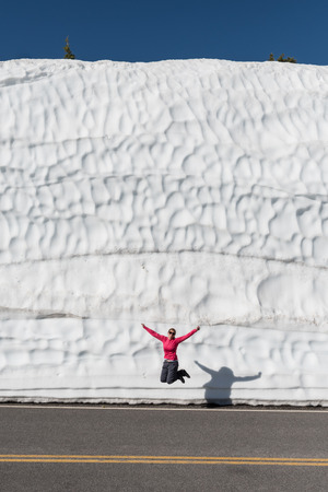 Woman Jumps in front of tall snow drift next to cleared road