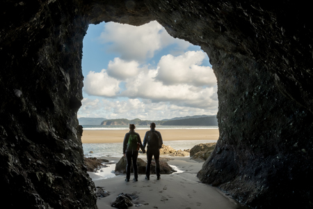 Hiker Couple Hold Hands In Sea Cave along Pacific coast