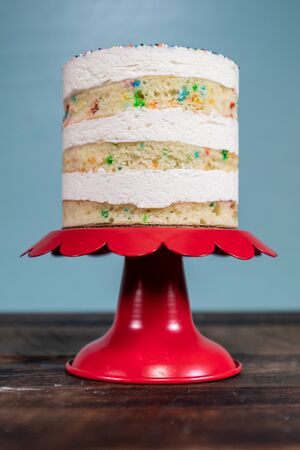 Red Cake Stand and Funfetti Cake on Blue Background vertical