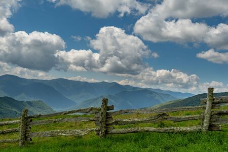 Wooden Fence Along Mountain Field on Cloudy Summer Day