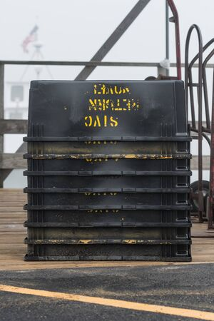 Black Bins Stacked on Dock on foggy day