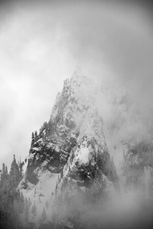 Niebla envuelve Pinnacle Peak cubierto de nieve en invierno Foto de archivo