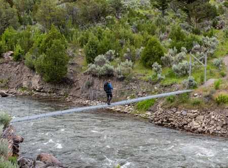 Man Crosses Footbridge Over Rushing River in Yellowstone Stok Fotoğraf