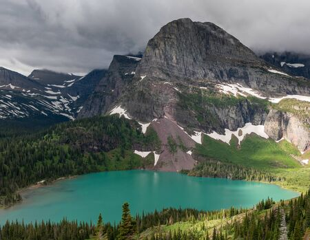 Sun Breaks Through Clouds Over Grinnell Lake and Mountain Stok Fotoğraf