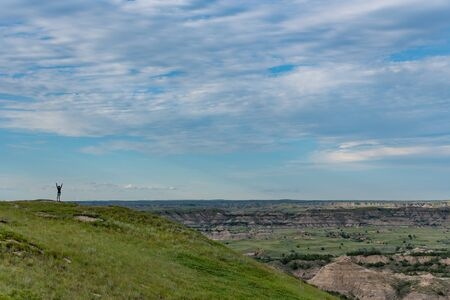 Woman Power Poses On Horizon over vast North Dakota wilderness