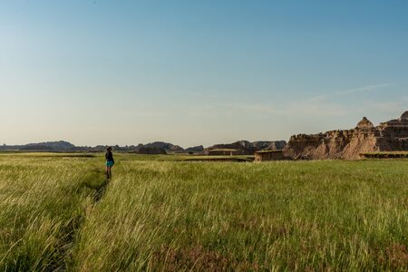 Woman Looks Out Over Badlands from Trail in Field