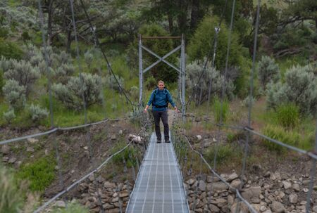 Man In Blue Shirt Stands On Suspension Bridge across river