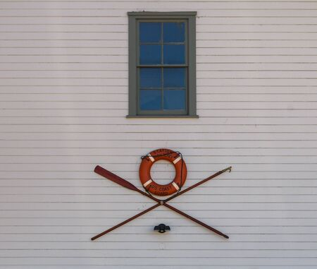 Oars and Life Preserver hangs on wall of white building 写真素材 - 131936992
