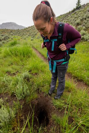 Woman Peers Into Large Hole Next to Trail