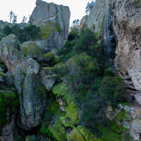 Woman Dwarfed by Giant Boulders along cliffside trail