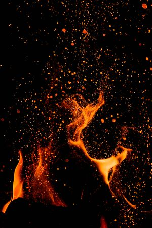 Flammen lecken, wenn Glut gegen den dunklen Himmel aufsteigt