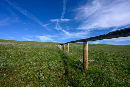 Low Angle of Wooden Fence with barbed Wire Across Green Field in summer