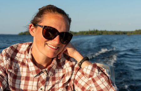 Woman in Sunglasses Smiles During Boat Ride Across Rainy Lake