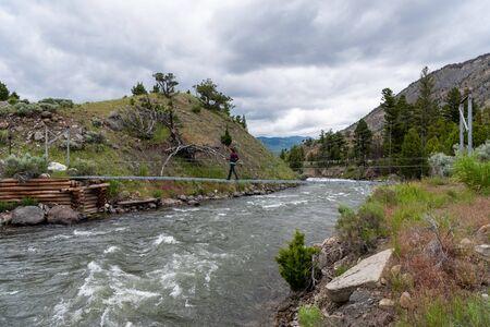 Woman Crosses Footbridge Over Rushing Water in Gardiner River