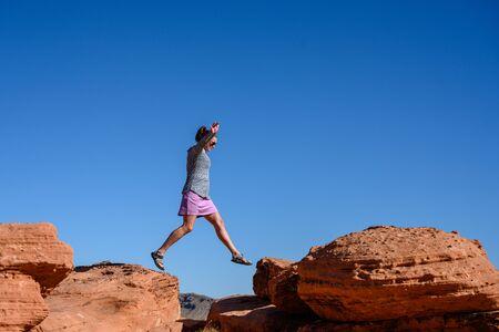 Woman Jumps Over Sandstone Boulders against blue sky