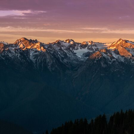 Pink Light from Sunrise Reflects Over Mountain Range in Washington Wilderness